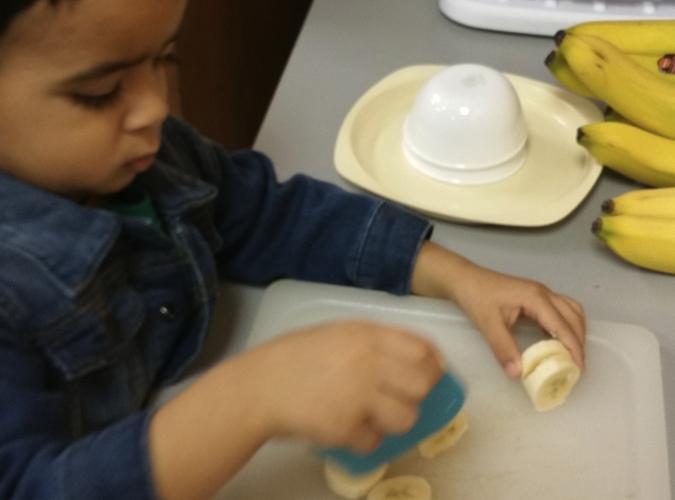 Toddler Veer slicing bananas